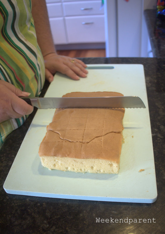 My friend carefully cutting the sponge cake into even squares
