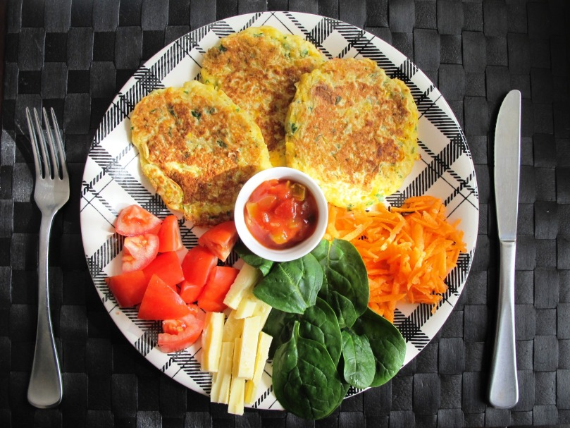 Corn fritters with tomatoes, cheese, spinach leaves, grated carrot, and salsa, served on a vintage plate