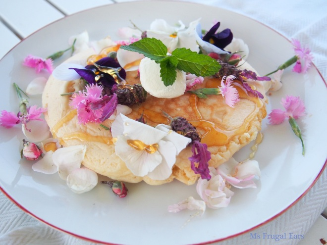 Pancakes on a plate with flowers and honey