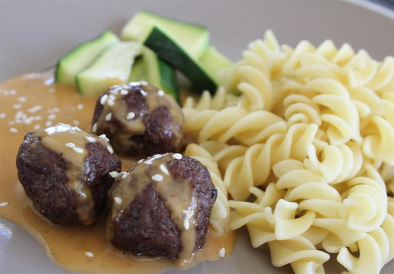 Red curry meatballs served with zucchinis and pasta
