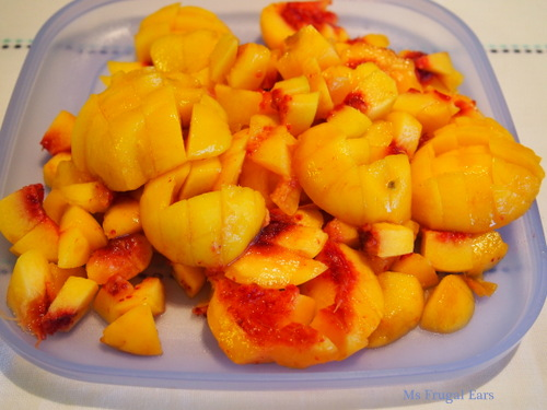 A pile of peaches sliced on a blue Tupperware plate