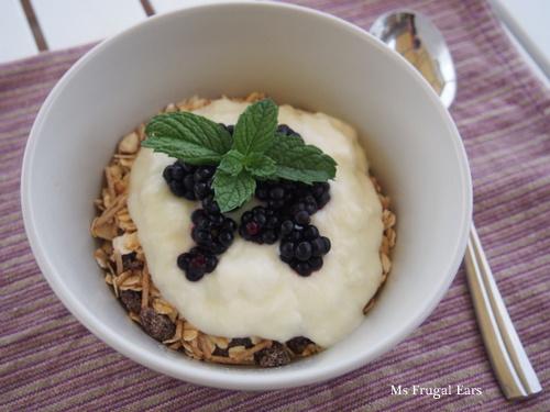 A bowl of homemade muesli, yoghurt, blackberries and mint