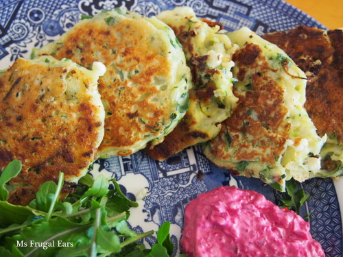 A close-up photo of zucchini fritters with rocket and beetroot dip