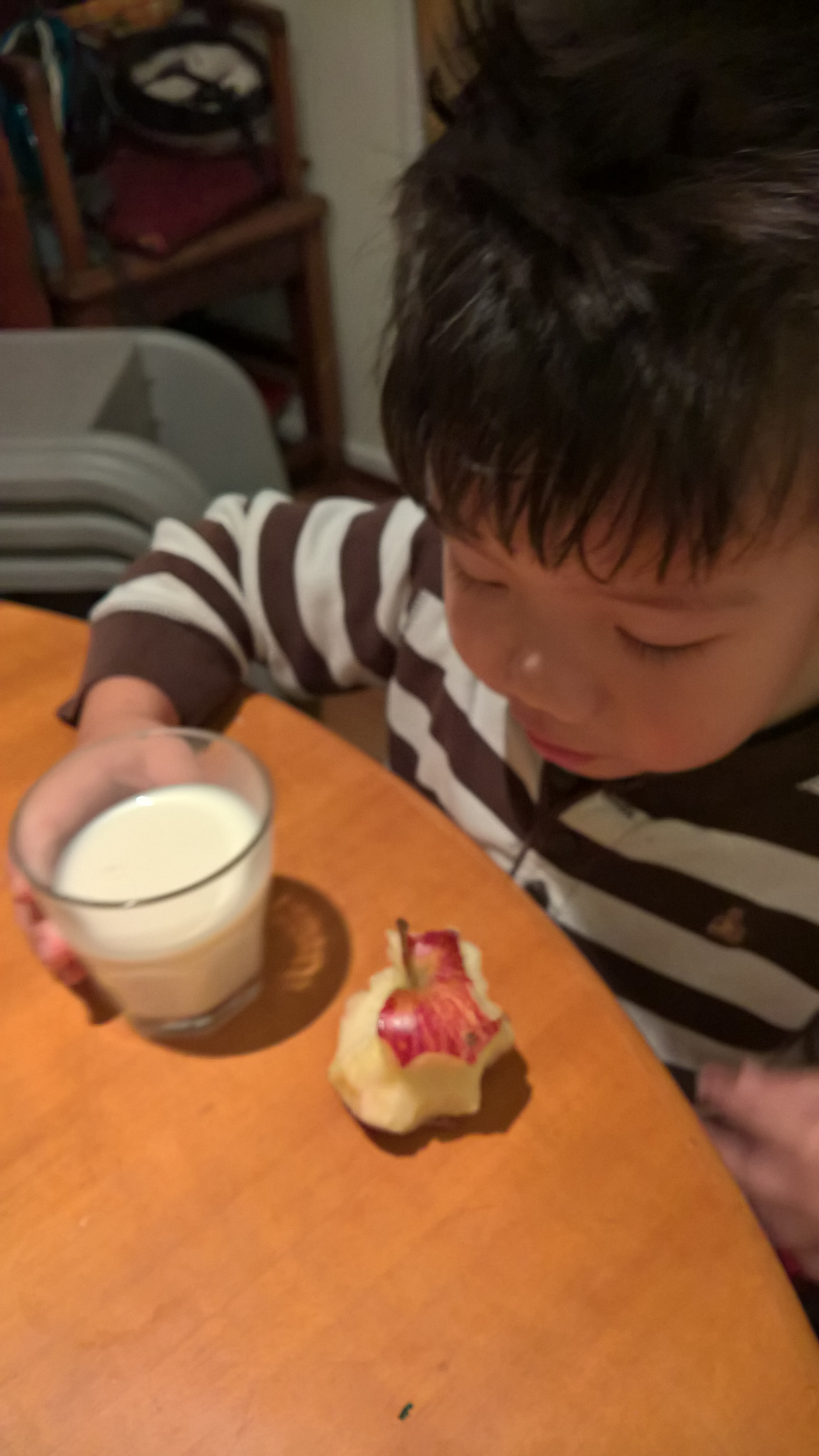 Little A drinking a glass of milk and eating an apple