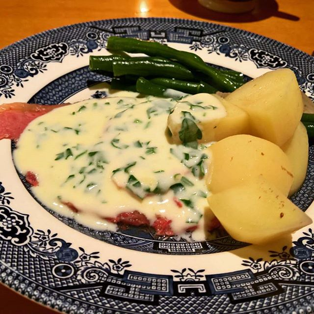 A plate of corned beef covered in white parsley sauce with potatoes and beans