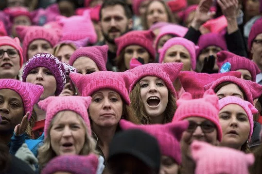 A group of people wearing pussy hats
